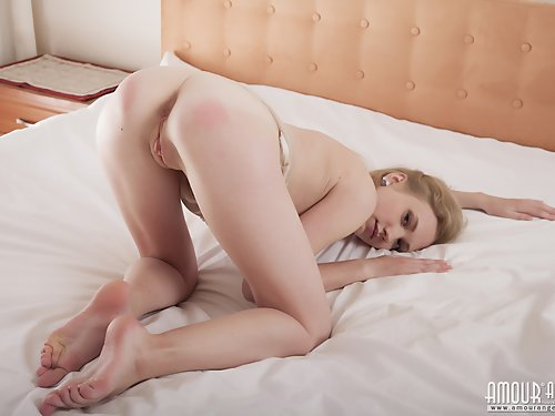 Busty blonde with pale skin spreading on her bed
