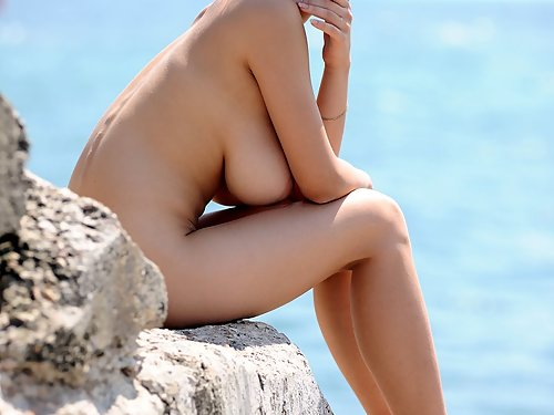 Amazing brunette with huge tits nude by the sea