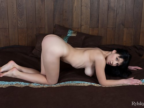 Busty black-haired girl spreading in bed