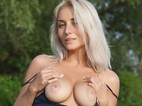 Shaved busty babe nude on a pier