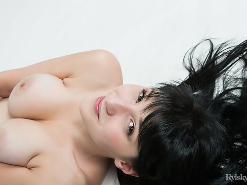Busty black-haired girl with large areolas spreads her legs