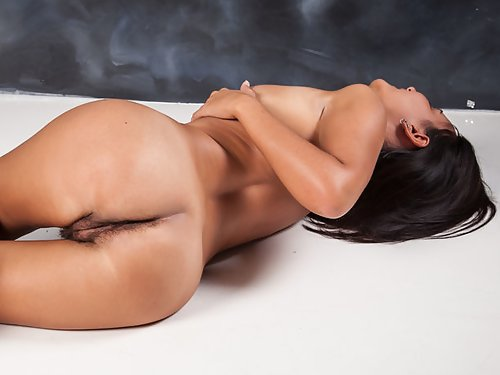 Busty black-haired babe shows off her hairy pussy