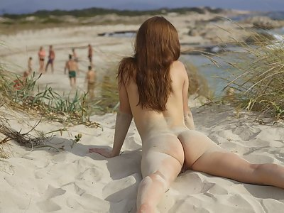 Adventurous brunette nude by a public beach
