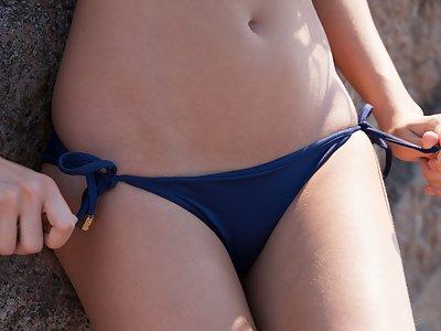 Slender brunette Lucy stripteases on the beach in the sun