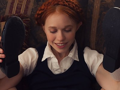 Redhead schoolgirl stripping on a couch