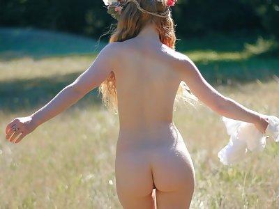 Petite redhead nude in a field
