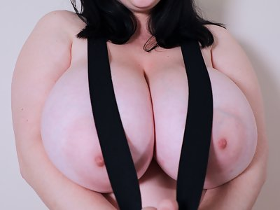 Chubby black-haired girl rubs lotion all over he huge tits