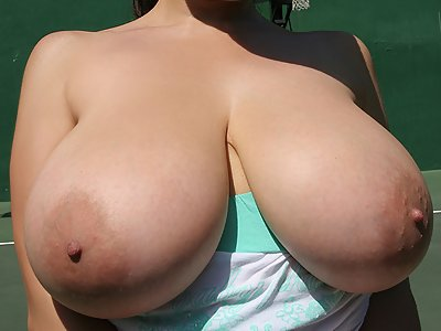 Brunette flashes her huge tits on the court