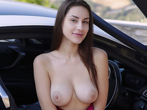 Shaved brunette with big tits nude by a sports car