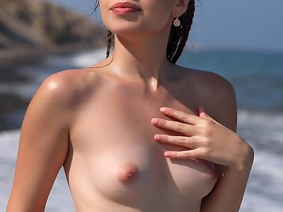 Blue-eyed girl with firm tits nude at the beach