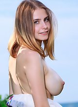 Busty blonde takes off her dress in a field