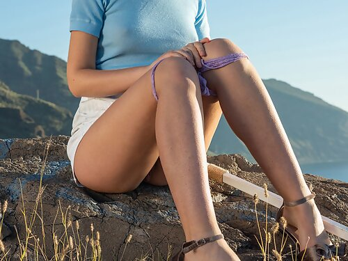 Cute redhead teen lifts up her skirt on a mountain