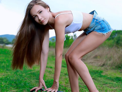 Sexy Mirabella takes off her jean shorts in a field