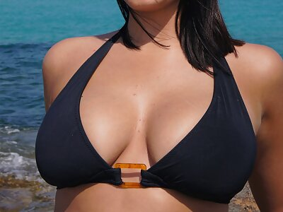 Brunette shows off her big natural tits at the beach