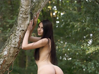 Long-haired brunette spreads her wet pussy in a forest