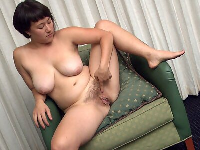 Busty brunette fingers her hairy pussy