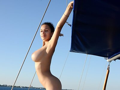 Busty brunette nude on a boat