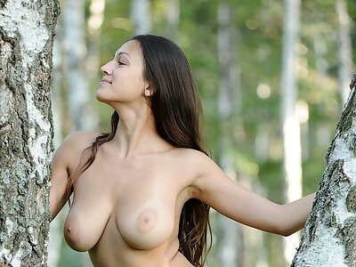 Busty brunette nude by a tree