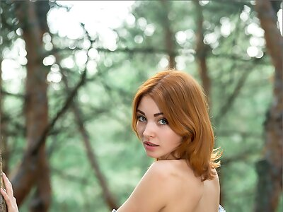 Busty redhead girl nude in a forest