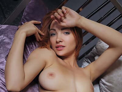 Gorgeous busty redhead spreads her shaved pussy