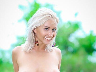 Busty blonde spreading in a field