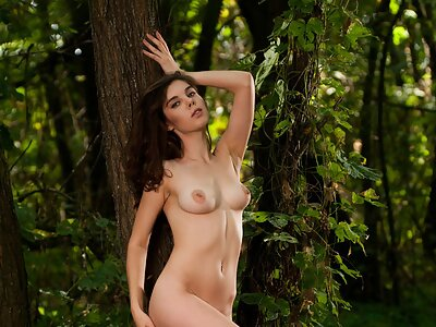 Brunette with meaty pussy lips nude in a forest