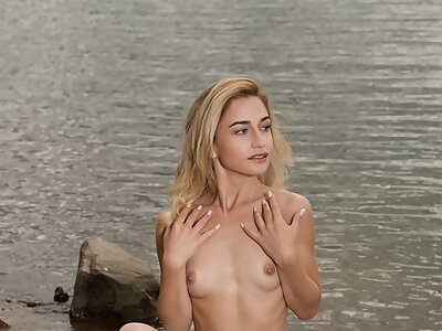 Shaved blonde shows off her big pussy lips at the beach