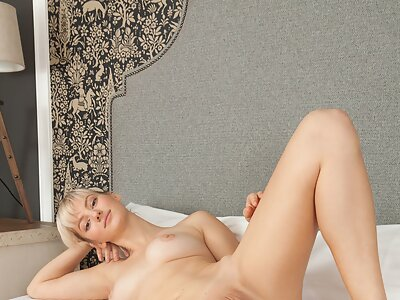 Cute blonde with firm tits spreading in bed