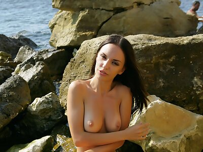 Black-haired babe with huge pussy lips in the sea