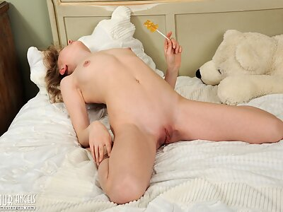 Cute blonde teen shows off her puffy pussy in bed