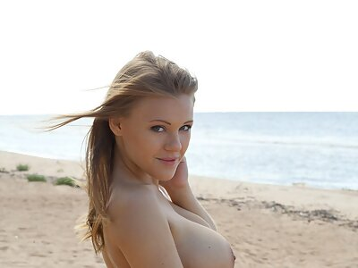 Busty freckled hottie nude at the beach