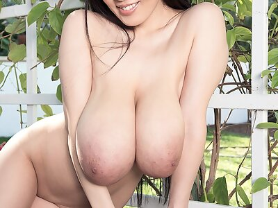 Sexy Asian Hitomi shows off her massive tits in the backyard