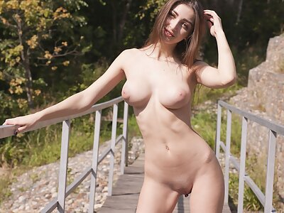 Shaved brunette with big firm tits on a bridge