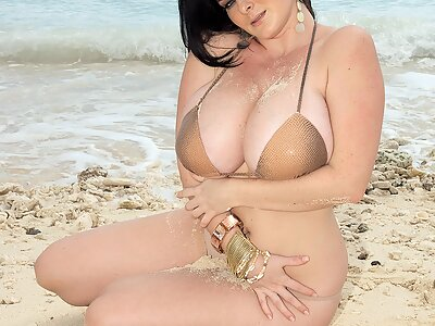 Busty freckled girl with black hair takes off her bikini at the beach