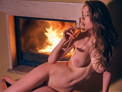 Busty brunette masturbating by the fireplace