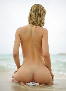 Gorgeous busty blonde sorts her butt plug at the beach