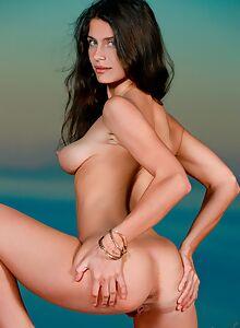 Sexy brunette spreads her ass outdoors