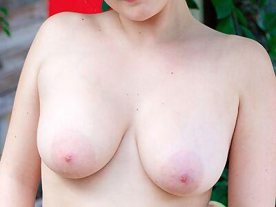Busty blonde stripping in the garden