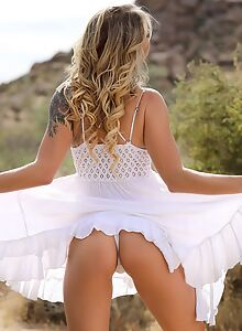 Tattooed blonde babe lifts up her dress in the desert