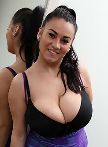 Chubby black-haired girl shows off her huge tits