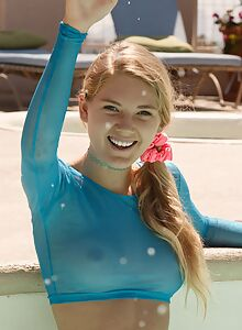 Cute blonde takes off her see-through top in the pool