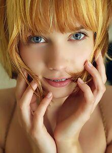 Cute redhead with blue eyes posing nude